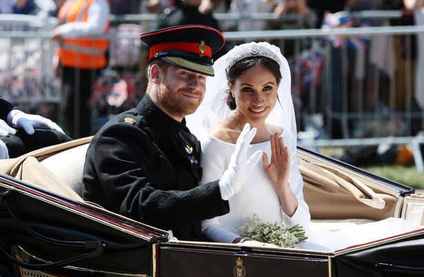 Prince Harry, Duke of Sussex and Meghan, Duchess of Sussex wave from the Ascot Landau Carriage during their carriage procession on Castle Hill outside Windsor Castle in Windsor