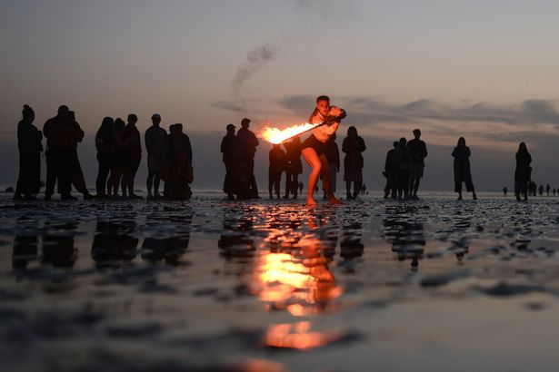 A fire juggler performs on Brighton beach
