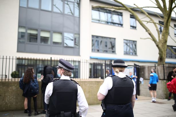 Police officers outside Pimlico Academy School, west London, where students staged a walk-out