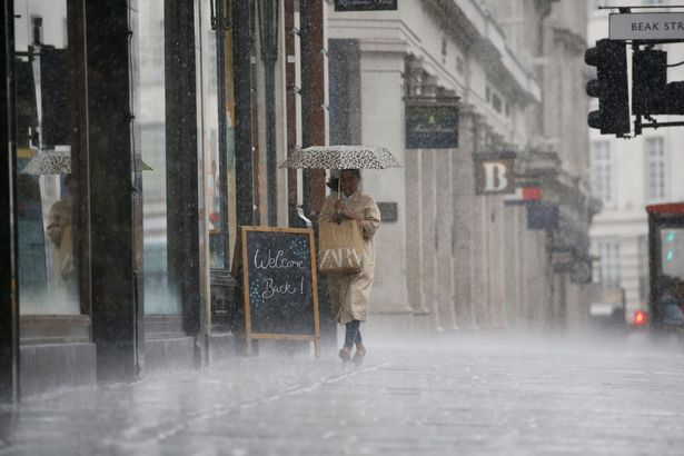 A shopper shelters from the rain