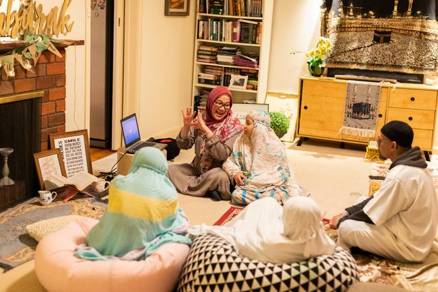 A family sitting around a laptop to watch short videos on teachings from the Quran