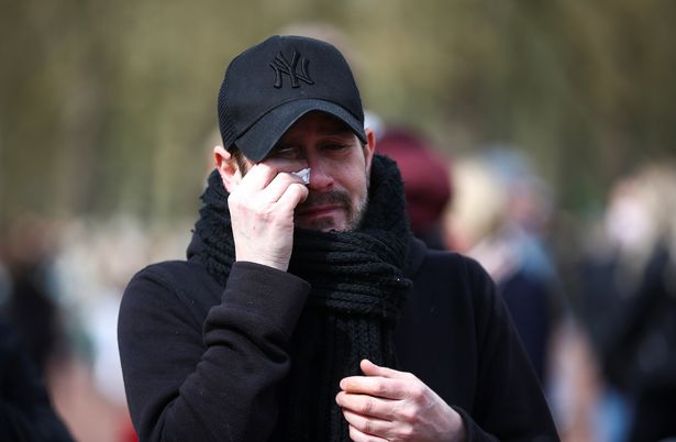 A mourner cries outside Buckingham Palace after it was announced that Prince Philip had died