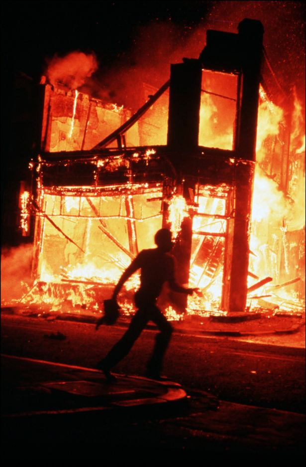 A man runs past a burning in Brixton during the riots