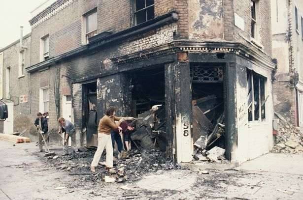 Workers clearing debris from a burnt-out welding shop in Railton Road, Brixton, after the Brixton riots in 1981.