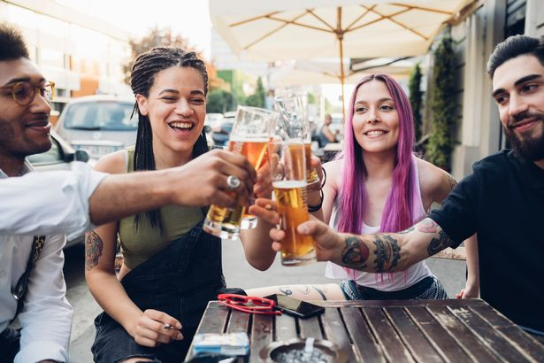 Happy friends clinking beer glasses outdoors at a bar