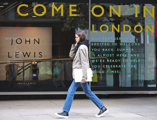 A sign in the window of John Lewis welcoming back customers, on Oxford Street, central London