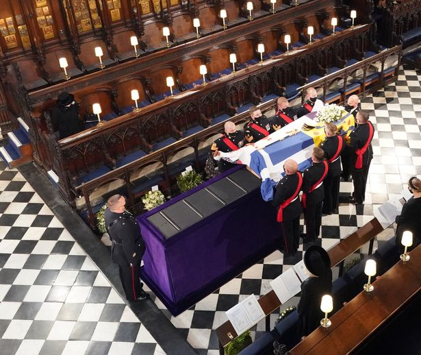 Queen Elizabeth II watches as pallbearers carry the coffin of the Duke of Edinburgh