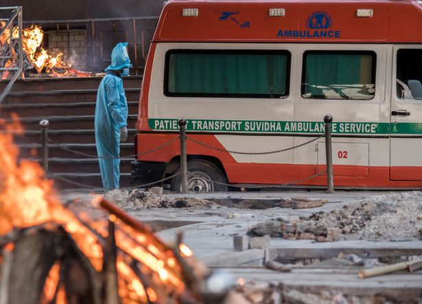 A man wearing PPE suit (personal Protection Equipment) waits to transfer the body of his relative who died of the Covid-19 coronavirus infection from an ambulance amid burning pyres of other covid deaths at a crematorium
