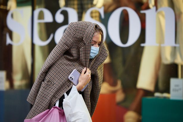 A woman covers her head on Oxford Street during heavy rain