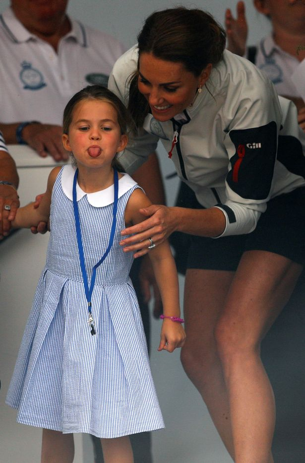 Princess Charlotte sticks her tongue out next to her mother, Catherine Duchess of Cambridge, before a presentation ceremony following the King's Cup Regatta in Isle of Wight