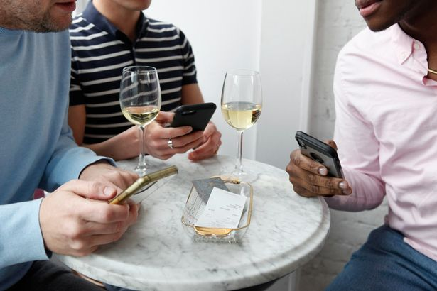 Three men look at a bill in a cafe and divide payment with mobile application close up