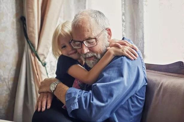 Happy smiling granddaughter hugging her grandfather