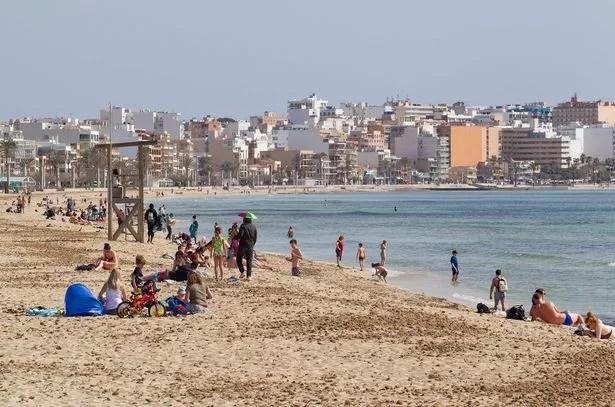 Tourists sunbathe on Palma Beach