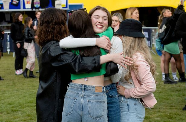 A group of women hug while attending a music festival in Liverpool during a Covid test event