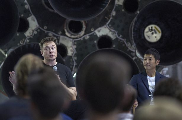 Elon Musk (L) and Japanese billionaire Yusaku Maezawa speak before a Falcon 9 rocket during the announcement that Maezawa will be the first private passenger who will fly around the Moon aboard the SpaceX BFR launch vehicle, at the SpaceX headquarters and rocket factory on September 17, 2018 in Hawthorne, California. - Japanese billionaire businessman, online fashion tycoon and art collector Yusaku Maezawa was revealed as the first tourist who will fly on a SpaceX rocket around the Moon. (Photo by DAVID MCNEW / AFP) (Photo by DAVID MCNEW/AFP via Getty Images)