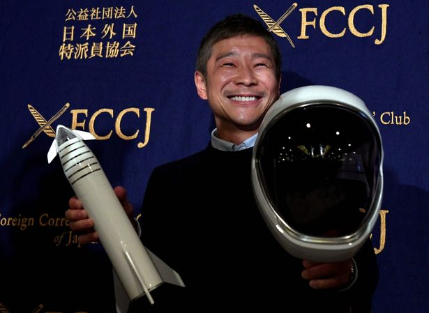 (FILES) This file photo taken on October 9, 2018 shows Yusaku Maezawa, entrepreneur and then-chief of online fashion company Zozo and SpaceX BFR's first private passenger, poses with a miniature rocket and space helmet prior to start of a press conference at the Foreign Correspondents' Club of Japan in Tokyo. - A Japanese billionaire has launched an online wanted ad -- a girlfriend who will fly around the Moon with him on a SpaceX rocket. The deadline to apply is January 17, 2020. (Photo by Toshifumi KITAMURA / AFP) (Photo by TOSHIFUMI KITAMURA/AFP via Getty Images)