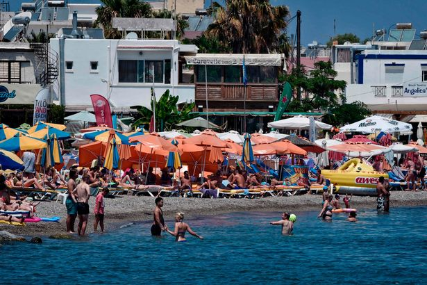 Tourists enjoy the sun and sea on a beach on the Greek Island of Kos on July 22, 2017