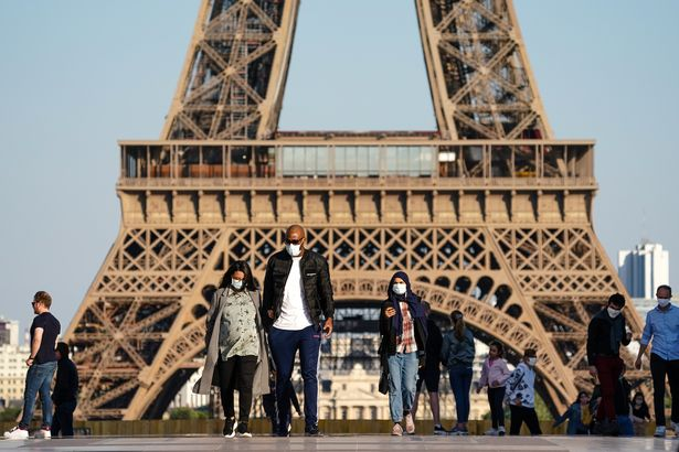 People wear protective masks at the Trocadéro in front of the Eiffel Tower