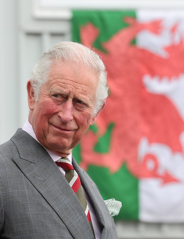 The flag of Wales is seen behind Prince Charles, Prince of Wales, during a visit by the supplier of protective, medical and defense equipment, BCB International, on May 14, 2021 in Cardiff, United Kingdom.