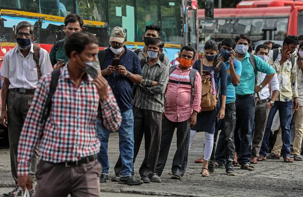 People in India wearing protective face masks wait for public transport at a bus stop in Mumbai