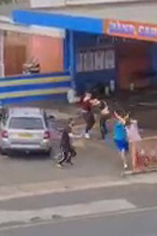 Men are seen throwing punches and trying to hit each other with metal poles