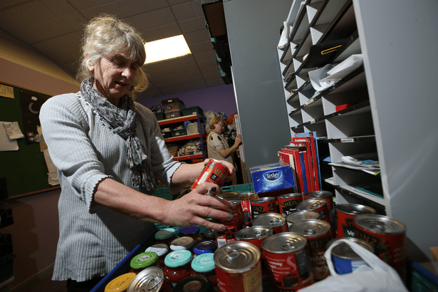 One volunteer packs a food parcel for a family in need of emergency help