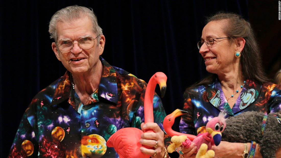 FILE - In this Thursday, Sept. 20, 2012 photo artist Don Featherstone, 1996 Ig Nobel Prize winner and creator of the plastic pink flamingo lawn ornament, poses with his wife Nancy while being honored as a past recipient during a performance at the Ig Nobel Prize ceremony at Harvard University, in Cambridge, Mass. Featherstone died Monday, June 22, 2015, at an elder care facility in Fitchburg, Mass., according to his wife, Nancy. He was 79. (AP Photo/Charles Krupa)