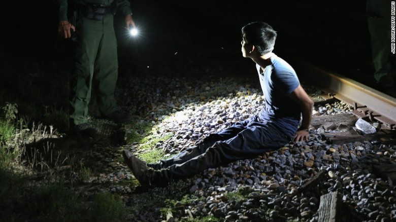 U.S. Border Patrol agents detain an undocumented immigrant at the border in 2014.