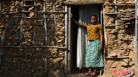 Christina John (14 years old) stands outside her house where she lives with her husband and her mother-in-law in Rebu village in Tarime district of Mara region in Tanzania. She was married when she was little over 13 years old. She managed to finish grade 7 before she was married off.Every year approximately 100-150 girls (ranging between 9 and 15 years) are gathered for female genital mutilation ceremony. When Christine turned 12, her mother along with other women from village took Christina and her friends to a nearby village for female genital mutilation (FGM).â??My mother had told me what would happen and she said it is a natural thing so I was not afraid. I did not realized how painful it will be. I donâ??t think it is right to circumcise girls because it is so painful. There are women who grow their nails especially scratch you with their long nails to remove the blood clots â?? it is so painful.â?After the procedure girls return and stay home for one month to allow their wound to heal. Once healed, they are considered ready for marriage. The community holds a â??ngomaâ?? ceremony where men come to select their wife. â??My father told me I had to get married because that is what women do after they have been circumcised.â?â??John gave my father 5 cows. My father bought me a few dishes. We got married after that and left to go live at Johnâ??s house. We live here with my mother-in-law and oldest brother-in-law.â?â??I donâ??t know how old John is. When I ask him he wonâ??t tell me, he says, why do you need to know my age. My mother says that he is 26. He works as a day labourer and load stones.â?â??My mother-in-law wants me to have six children, but how will I educate them, how will I provide for six children? My mother-in-law also says that I will get pregnant if I take traditional medicine. But I refuse to take this medicine. I want to have three children, but I want to wait until Iâ??m about 18 or 20.â?â??I donâ??t