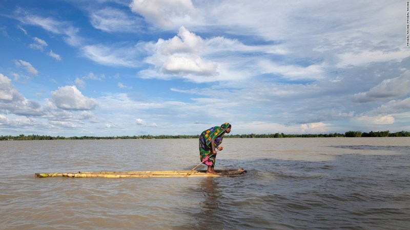 "Photo: Probal Rashid. ""A flood-affected woman on a raft approaches a boat, searching a dry place to shelter herself in Islampur, Jamalpur, Bangladesh. Bangladesh is one of the countries most vulnerable to the effects of climate change,"" wrote Rashid."