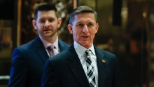 Retired Lt. Gen Michael Flynn talks to media as he arrives at Trump Tower in New York with his son, Michael Flynn Jr., behind him.