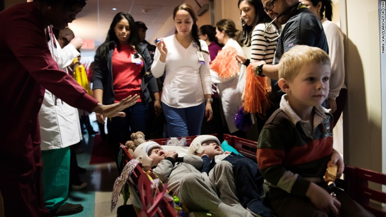 Jadon, left, and Anias McDonald look up at hospital staff as they leave their room at Montefiore Children's Hospital in New York on Wednesday, December 14. Their older brother, Aza, proudly sits at the front of the wagon.