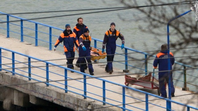 """Russian emergency workers carry remains from the wreckage of the Tu-154 that crashed near Sochi, Russia, on Sunday. The plane was carrying more than 60 members of the Russian army's popular Alexandrov Ensemble, dubbed """"Russia's singing weapon."""""""