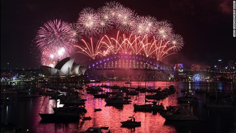 Fireworks illuminate the sky over the Opera House and Harbour Bridge in Sydney, Australia.
