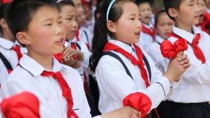 Chinese students wearing the uniform of the Young Pioneers.