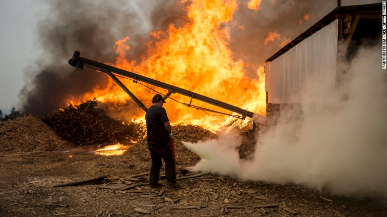 Men work to put out a raging fire in Constitucion, about 220 miles south of Santiago, the capital.