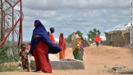 A refugee stands with her son just outside a fenced perimeter at Dadaab in May 2015.