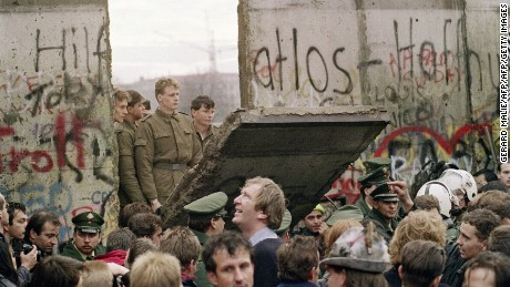 """TO GO WITH AFP STORY by  Audrey KAUFFMANN and PACKAGE """"Germany-east-History-20years""""  FILES - West Berliners crowd in front of the Berlin Wall early 11 November 1989 as they watch East German border guards demolishing a section of the wall in order to open a new crossing point between East and West Berlin, near the Potsdamer Square. Two days before, Gunter Schabowski, the East Berlin Communist party boss, declared that starting from midnight, East Germans would be free to leave the country, without permission, at any point along the border, including the crossing-points through the Wall in Berlin. The Berlin concrete wall was built by the East German government in August 1961 to seal off East Berlin from the part of the city occupied by the three main Western powers to prevent mass illegal immigration to the West. According to the """"August 13 Association"""" which specialises in the history of the Berlin Wall, at least 938 people - 255 in Berlin alone - died, shot by East German border guards, attempting to flee to West Berlin or West Germany.   AFP PHOTO / GERARD MALIE (Photo credit should read GERARD MALIE/AFP/Getty Images)"""