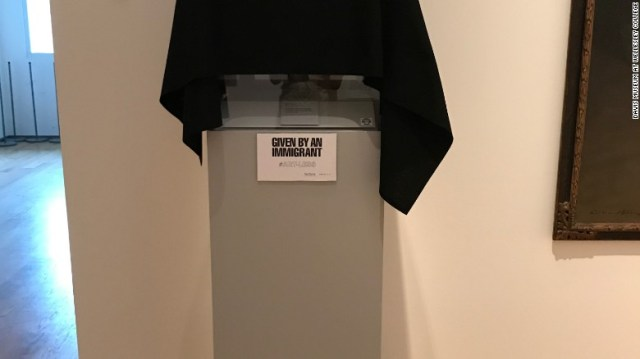Black cloth covers art that was given by an immigrant to the Davis Museum.