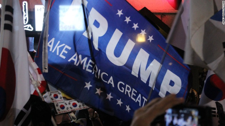 """Park supporters wave a Donald Trump campaign flag. """"We want to make Korea great again,"""" they said."""