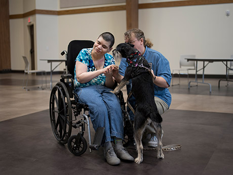 Lesli pushed away bean bags and rubber balls but welcomed the chance to pet Omri with his handler's help.