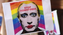 MADRID, SPAIN - AUGUST 23:  A protestor holds up an image representing Russian President Vladimir Putin wearing lipstick during a protest against Russian anti-gay laws opposite the Russian embassy on August 23, 2013 in Madrid, Spain. Gay protestors are protesting Russia's new anti-gay laws and demanding the cancellation of the upcoming 2014 Winter Olympics scheduled to be held in Sochi, Russia.  (Photo by Denis Doyle/Getty Images)