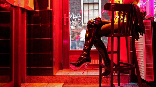 Un operaio del sesso attende affari in una finestra di Amsterdam & # 39; s Red Light District.