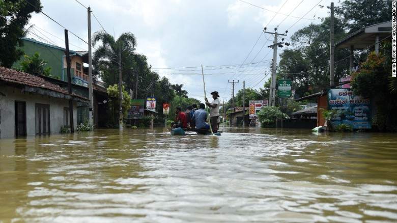 Sri Lankan residents travel by boat through floodwaters in the suburb of Kaduwela in the capital Colombo on May 28, 2017.
