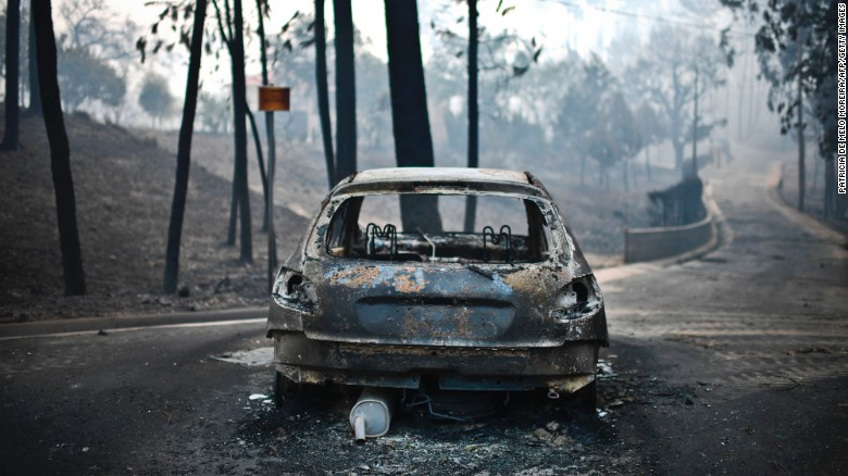 A burned out car sits on the road after a wildfire in Pedrogao, central Portugal, on June 18.