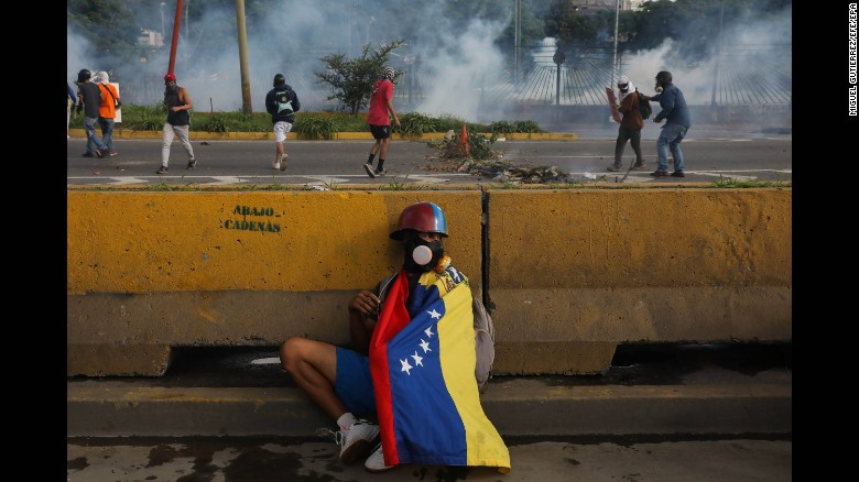 """A protester hides behind a barrier in Caracas, Venezuela, on Thursday, June 22. The country <a href=""""http://www.cnn.com/2017/05/09/americas/venezuela-violin-protester/"""" target=""""_blank"""">has witnessed widespread unrest</a> since March 29, when the Venezuelan Supreme Court dissolved Parliament and transferred all legislative powers to itself. Though the decision was reversed three days later, protests continue across the country, which is in the midst of an economic crisis."""