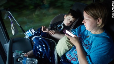 Gabe Michot, 4, holds his mother's arm as he sleeps on the bus.