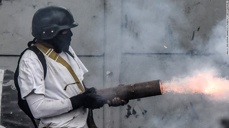 A protester shoots a firework from a pipe at national guard members during clashes Friday, July 28, in Caracas. Demonstrators blocked some streets in the capital in defiance of President Nicolás Maduro's ban on protests ahead of a controversial election. The vote will elect a special assembly aiming to rewrite the constitution at Maduro's request, and follows months of sometimes deadly protests.