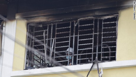 A forensic police officer investigates burned windows at an Islamic religious school following a fire on September 14, on the outskirts of Kuala Lumpur, Malaysia.