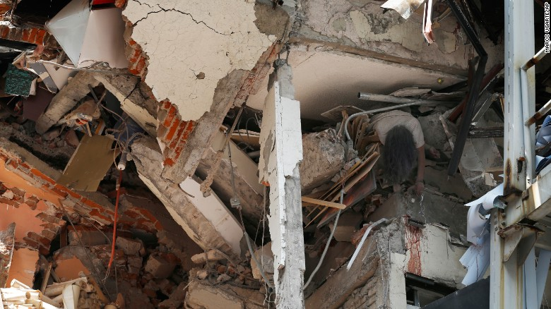 A woman's crushed body hangs from a collapsed building in Mexico City on September 19.